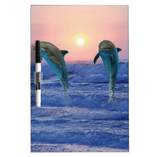 Delfínes en la salida del sol pizarras blancas de calidad