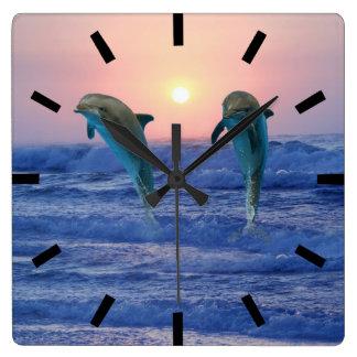 Delfínes en la salida del sol reloj cuadrado