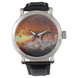Delfínes en nubes en el collage de la puesta del relojes de mano