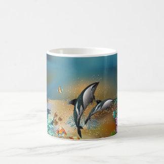 Delfínes lindos de los pares que juegan en el taza