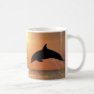Delfínes por puesta del sol taza