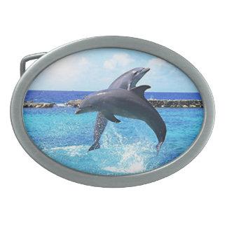 Delfínes que juegan en el océano hebilla de cinturon oval