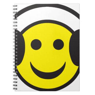 Delirio sonriente de la cara del auricular libro de apuntes con espiral