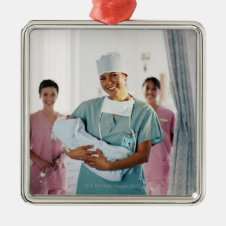 Delivery room nurse holding baby, nurses in christmas tree ornaments