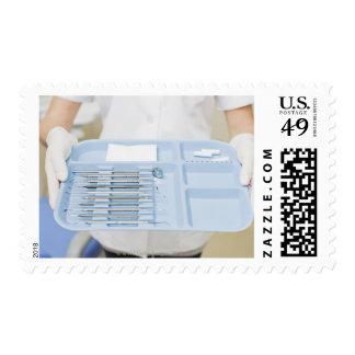 Dental hygienist  holding tray of dental postage