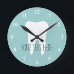"""Dentist office wall clock with tooth logo<br><div class=""""desc"""">Dentist office wall clock with tooth logo and personalizable text for name or slogan. Great design for the waiting room of your dental clinic or hygienist practice.</div>"""