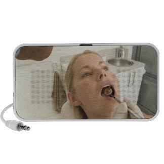 Dentista que mira los dientes de los pacientes iPod altavoz