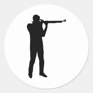 Deportes que tiran el rifle etiqueta redonda