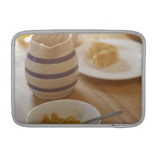 Desayuno comido mitad en la tabla de cocina funda macbook air