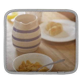 Desayuno comido mitad en la tabla de cocina manga de iPad