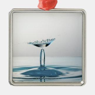 Descensos del agua que chocan para formar un adorno navideño cuadrado de metal