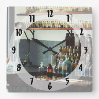 Desk With Bottles of Chemicals Square Wall Clock