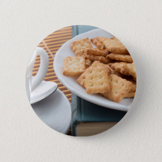Detail of a cup of tea and a plate of crackers button