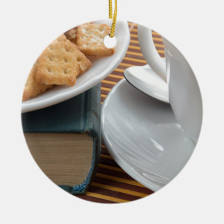 Detail of a cup of tea and a plate of crackers ceramic ornament