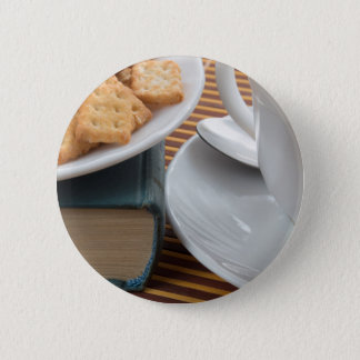 Detail of a cup of tea and a plate of crackers pinback button