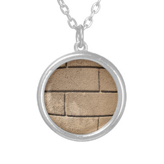 Detail of a wall covered with cement round pendant necklace