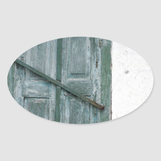 Detail of a wall with wooden shutters oval sticker