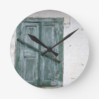 Detail of a wall with wooden shutters round clock