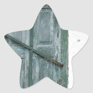 Detail of a wall with wooden shutters star sticker