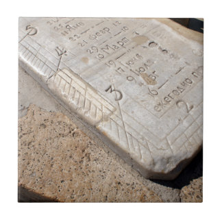 Detail of ancient stone dial sundial closeup small square tile