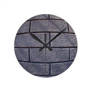 Detalle de una pared cubierta con el cemento reloj redondo mediano