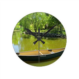 Día de verano soleado con la canoa en el agua reloj redondo mediano