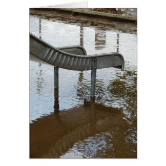 Diapositiva y reflexión inundadas del patio tarjetón