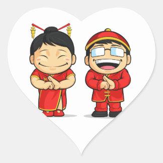 Dibujo animado del muchacho y del chica chinos pegatina en forma de corazón