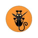 Dibujo animado divertido del gato negro que rasguñ reloj