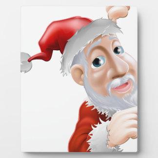 Dibujo animado feliz Santa que señala al lado Placa