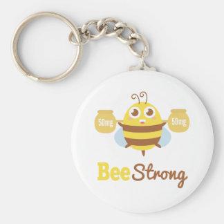 Dibujo animado fuerte de la abeja graciosamente y  llavero redondo tipo pin