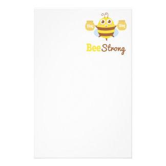 Dibujo animado fuerte de la abeja graciosamente y  papelería