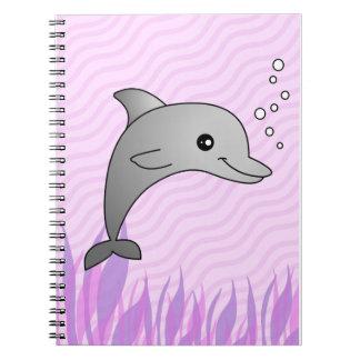 Dibujo animado gris lindo del delfín en agua rosad cuaderno