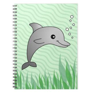 Dibujo animado gris lindo del delfín en agua verde libros de apuntes con espiral