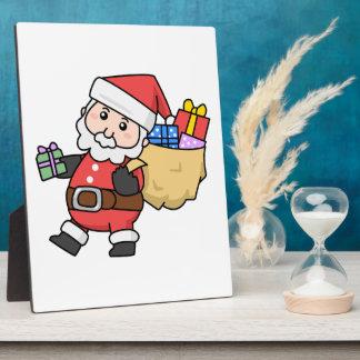 Dibujo animado Papá Noel que lleva un bolso de jug Placa Para Mostrar
