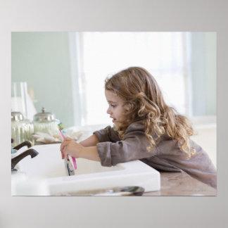 Dientes de cepillado de la niña linda en el fregad póster