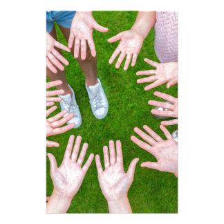 Diez brazos de niños en círculo con las palmas de papelería de diseño