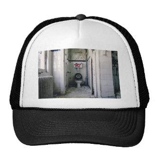 Dilapidated bathroom with graffiti trucker hat