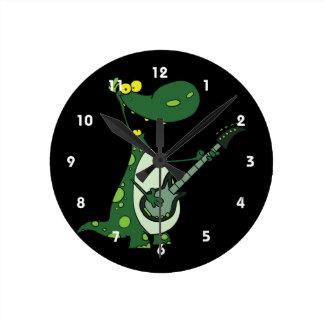 Dino verde que sostiene la guitarra gráfica reloj redondo mediano