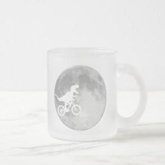 Dinosaurio en una bici en cielo con la luna taza de café