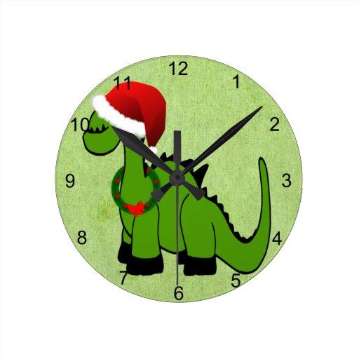 Dinosaurio verde en un gorra de Santa para el navi Reloj