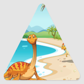 Dinosaurs living on the beach triangle sticker