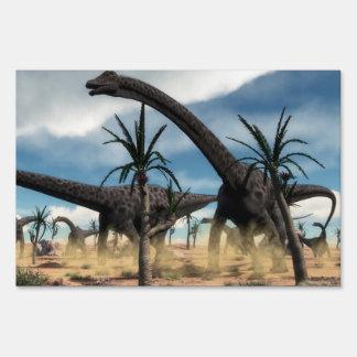 Diplodocus dinosaurs herd in the desert lawn sign