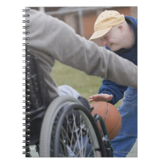 Disabled man playing basketball with his son spiral notebook