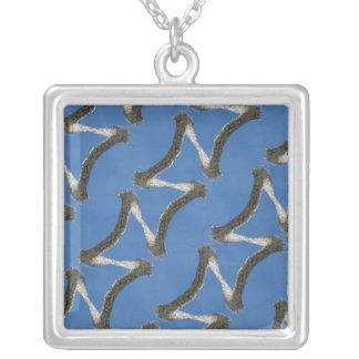 Diseño azul del caleidoscopio con la rama de árbol colgante cuadrado