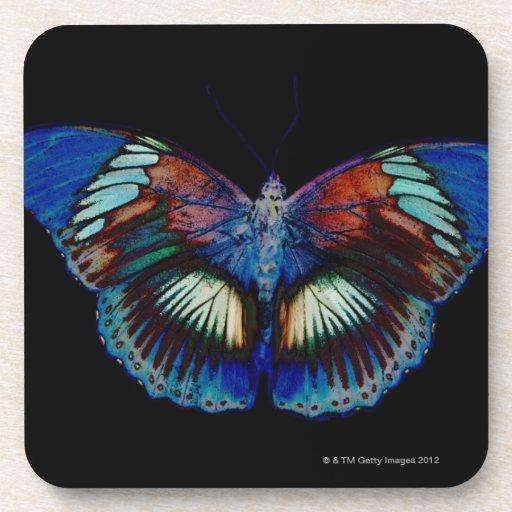 Diseño colorido de la mariposa contra el contexto posavasos de bebidas