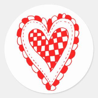 Diseño con volantes de los bordes del corazón rojo etiqueta redonda