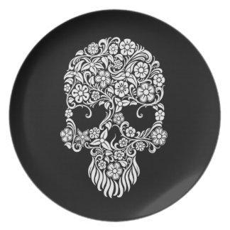 Diseño del cráneo de las flores blancas y de las v plato de cena