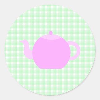 Diseño rosado de la tetera en control verde etiqueta redonda