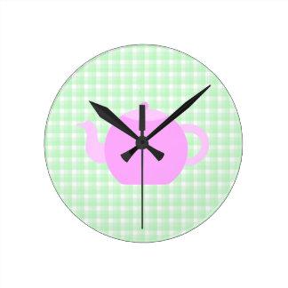 Diseño rosado de la tetera en control verde relojes